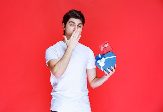 Mann, der herzform-geschenkboxen hält und flirtet.