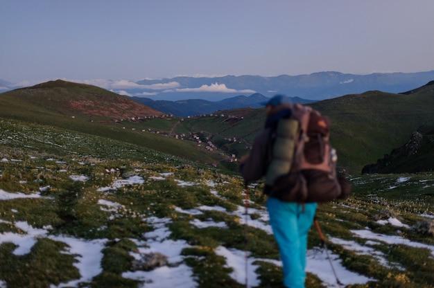 Mann der hinteren ansicht, der auf das feld mit schneeresten mit dem wandern des rucksacks und der stöcke geht