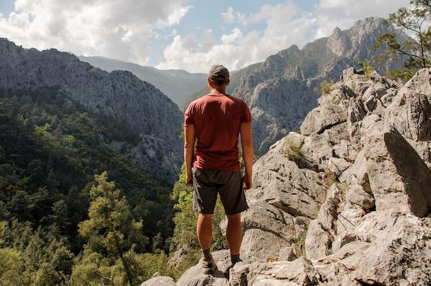 Mann der hinteren ansicht, der auf dem felsen auf der schönen landschaft steht