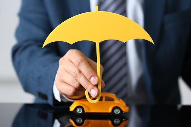 Mann, der hölzernen regenschirm über auto hält