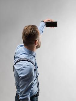 Mann, der horizontal smartphone auf weiß hält