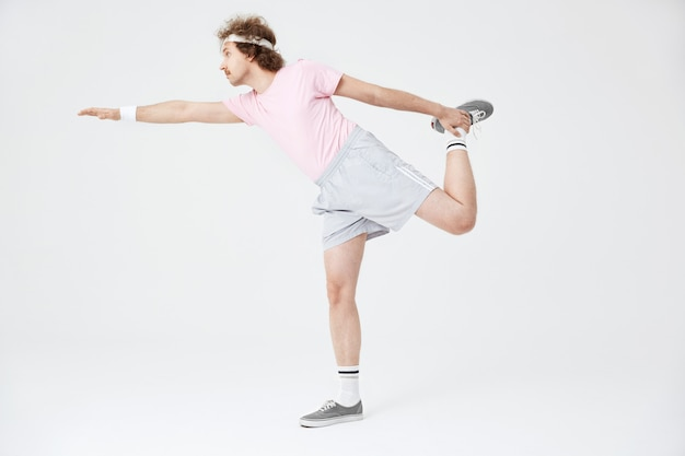 Mann, der horizontale position auf einem bein mit der hand nach oben tut