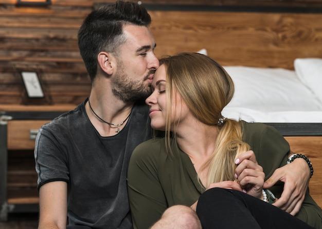 Mann, der ihre freundin auf ihrer stirn küsst