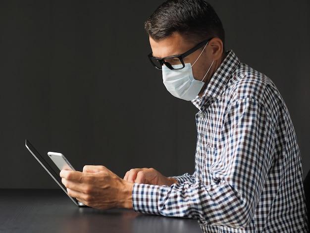 Mann, der im arbeitsbereich zu hause mit laptop und handy arbeitet, während er medizinische maske trägt, zum des schutzes und der verhinderung der infektion des koronavirus oder des covid-19.
