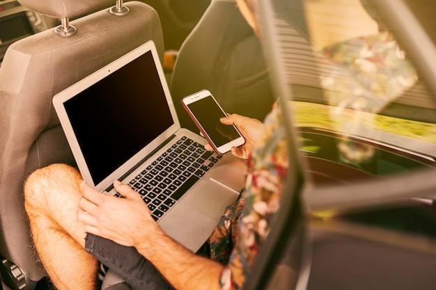 Mann, der im auto mit laptop und smartphone sitzt
