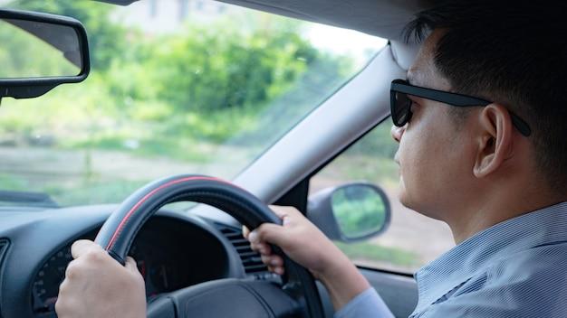 Mann, der im auto mit sonnenbrille fährt