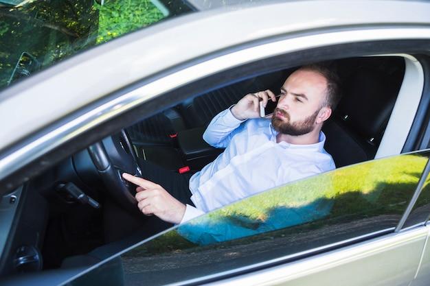 Mann, der im auto spricht auf smartphone sitzt