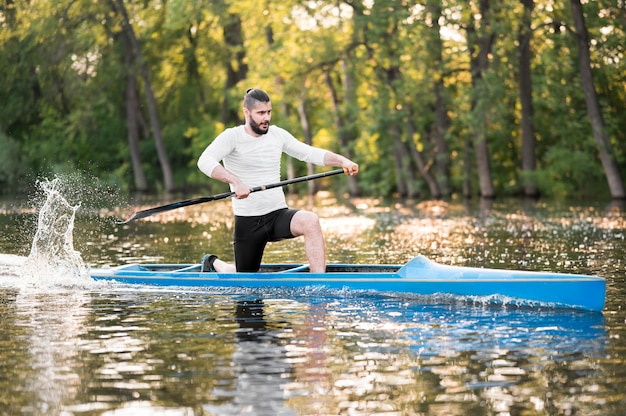 Mann, der im blauen kanu paddelt