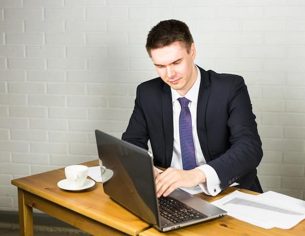 Mann, der im büro am laptop arbeitet