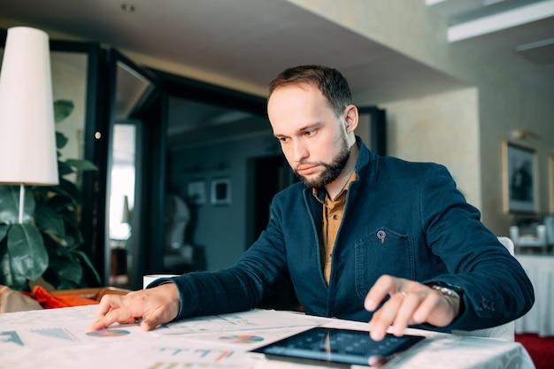Mann, der im büro arbeitet und einige statistische berechnungsberichte analysiert.