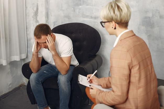 Mann, der im büro des psychologen sitzt und über probleme spricht