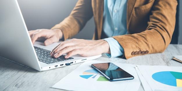 Mann, der im computer am schreibtisch arbeitet