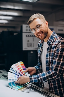Mann, der im druckhaus mit papier und farben arbeitet