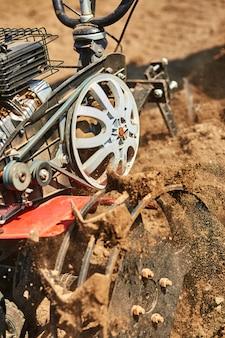 Mann, der im garten mit gartenfräse arbeitet. gartenfräse zur arbeit, nahaufnahme. mann mit traktor, der feld im frühjahr kultiviert. moderne landwirtschaft, technologische landwirtschaft.