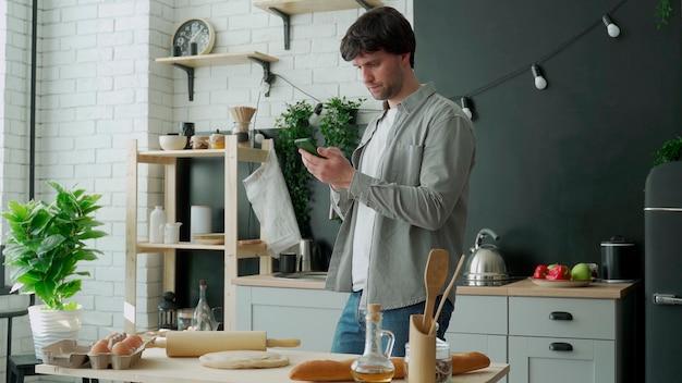Mann, der im internet mit telefon steht, das in der küche steht