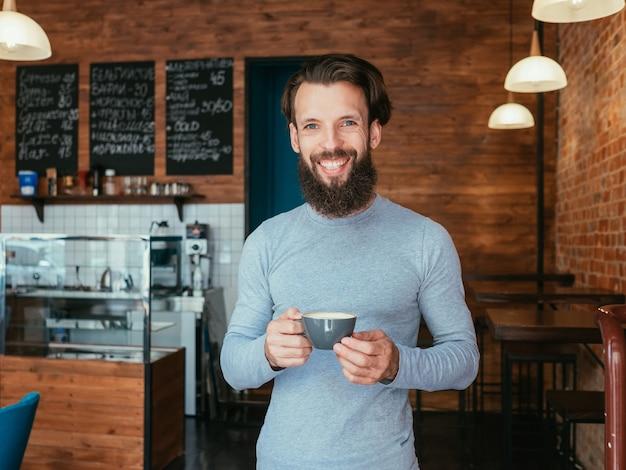 Mann, der im kaffeehaus steht, der tasse cappuccino hält
