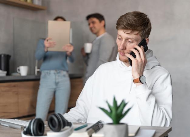 Mann, der im medienfeld arbeitet, das auf smartphone spricht, während kollegen tablet betrachten