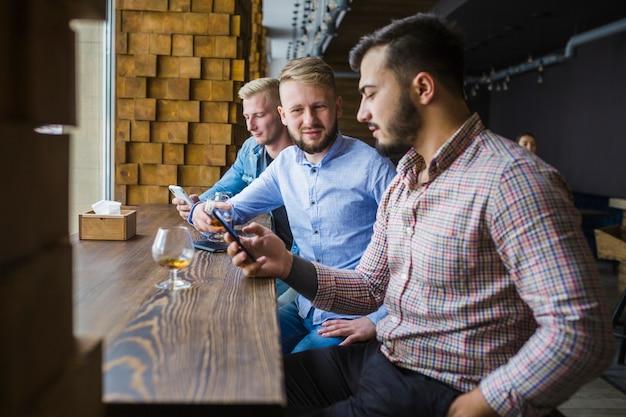 Mann, der im restaurant mit seinen freunden verwendet handy sitzt