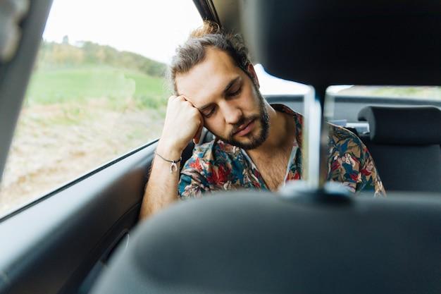Mann, der im rücksitz des autos schläft