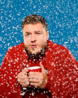 Mann, der im schnee beim halten einer schale bleibt