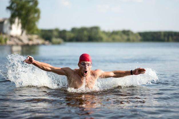 Mann, der im see schwimmt