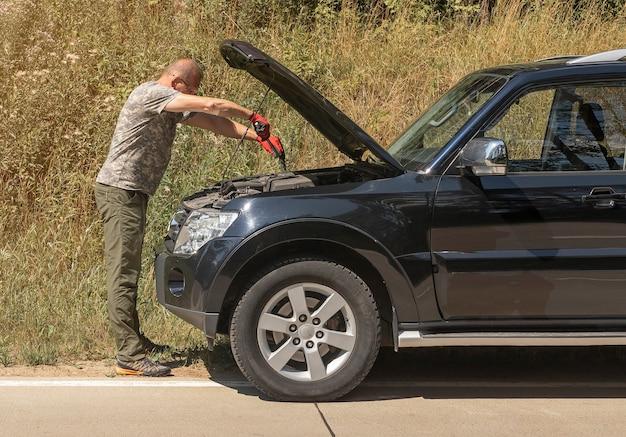Mann, der im sommer mit mechanischem werkzeug in der nähe des autos mit haube im freien steht und es nach dem auto repariert ...
