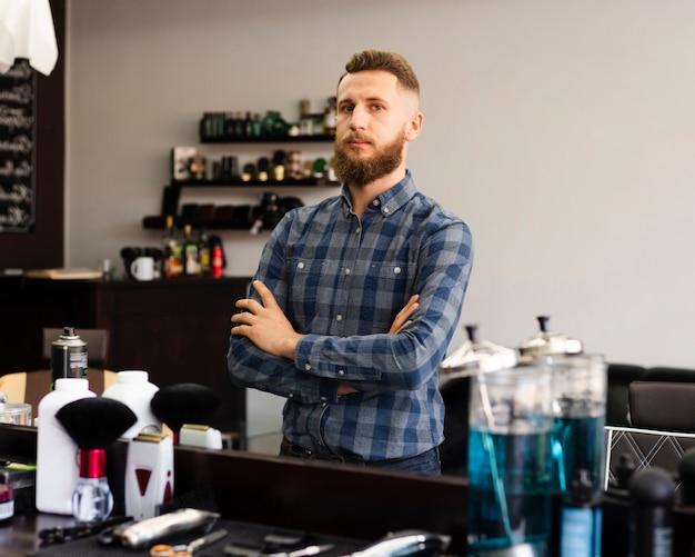 Mann, der im spiegel eines friseursalons sich betrachtet