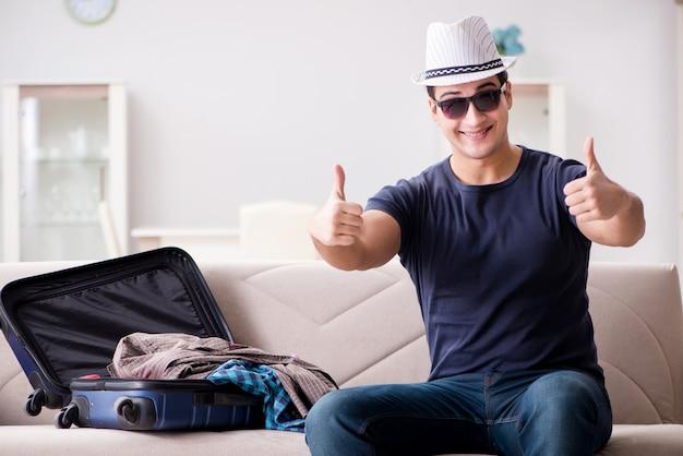 Mann, der im urlaub seinen koffer packend geht