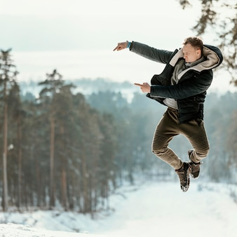 Mann, der im winter im freien in der natur springt und auf kopierraum zeigt