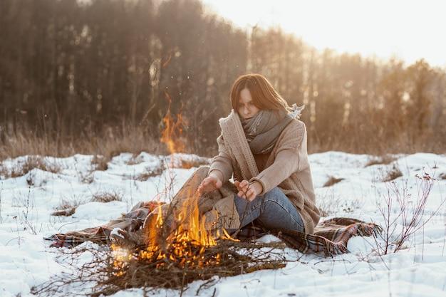 Mann, der im winter neben einem lagerfeuer aufwärmt