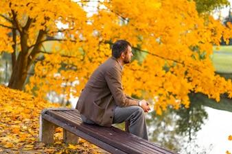Mann, der in den Herbstpark geht