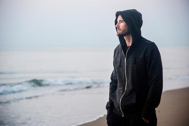Mann, der in der einsamkeit am strand geht