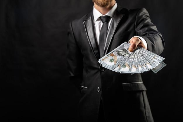 Mann, der in der hand geld am schwarzen hält