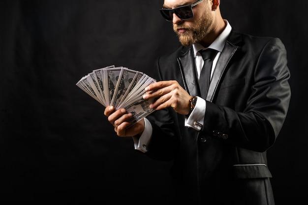 Mann, der in der hand geld am schwarzen hält Premium Fotos
