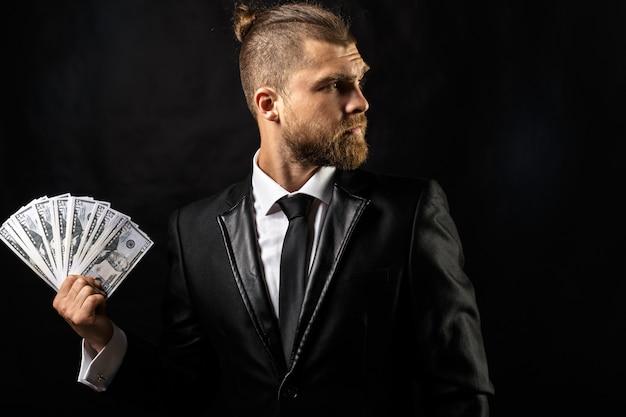 Mann, der in der hand geld am schwarzen hintergrund hält