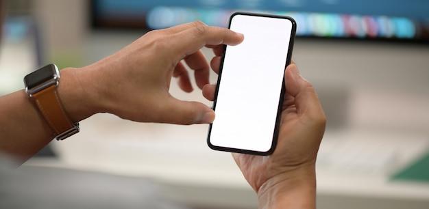 Mann, der in der hand mobilen smartphone des weißen schirmes des isolats sitzt und hält