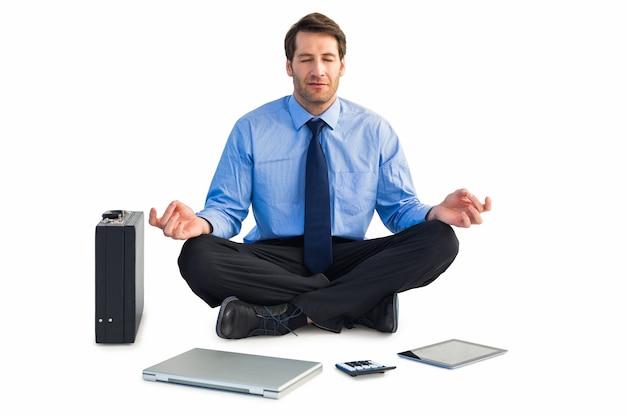 Mann, der in der lotoshaltung mit laptop, tablette und koffer sitzt Premium Fotos
