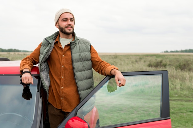 Mann, der in der natur aus dem auto steigt