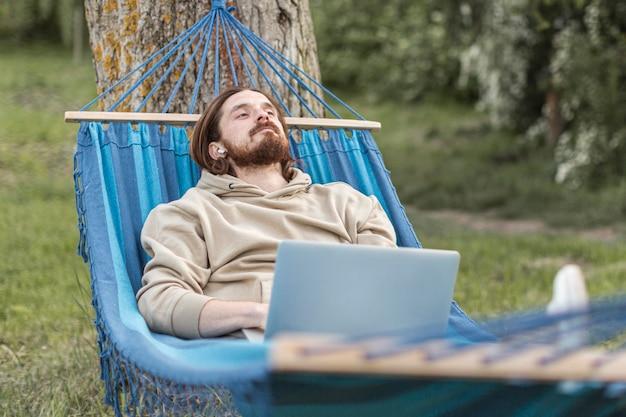 Mann, der in der natur beim sitzen in der hängematte entspannt