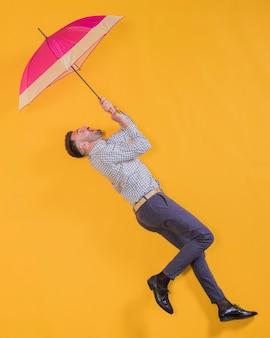 Mann, der in die luft mit einem regenschirm schwimmt