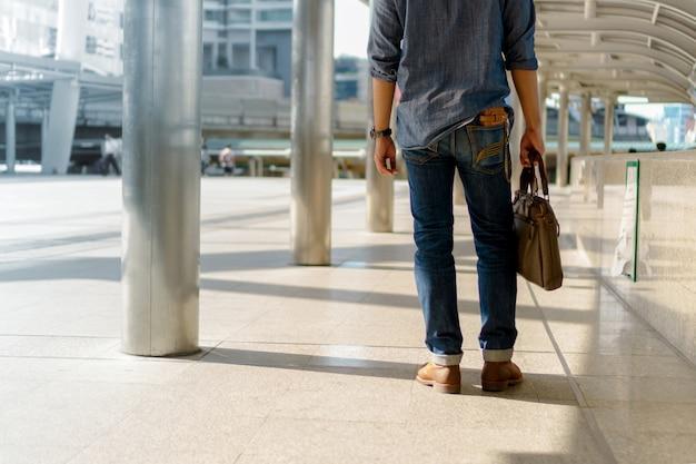 Mann, der in die stadt geht und laptoptasche hält