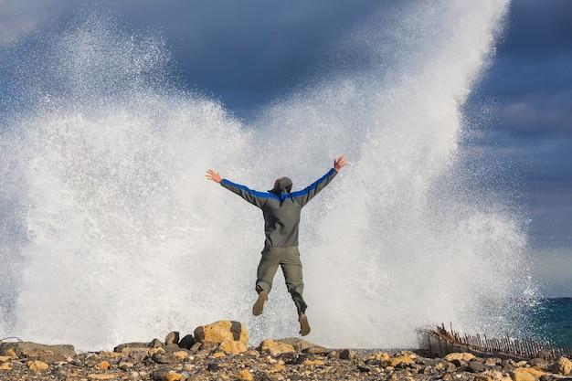 Mann, der in dramatischen sturmwellen springt