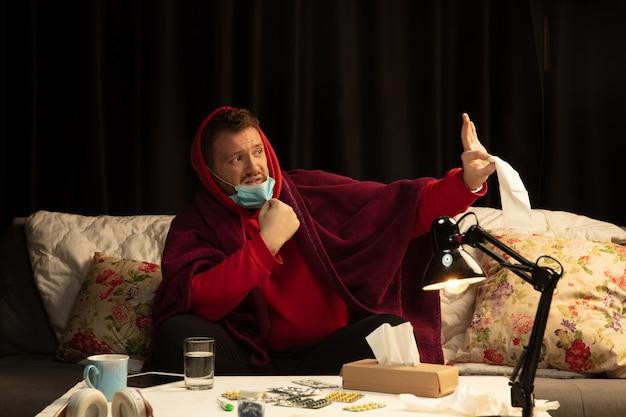 Mann, der in ein plaid gehüllt ist, sieht krank, krank, niesend und hustend aus, wenn er drinnen zu hause sitzt