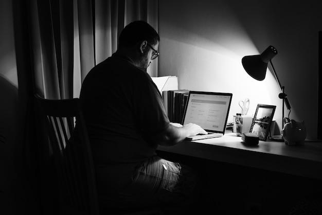 Mann, der in einem dunklen innenministerium mit einem laptop arbeitet