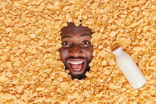 Mann, der in einem haufen cornflakes mit einer flasche milch in der nähe begraben ist, hält den mund weit geöffnet hat eine glückliche stimmung drückt positive emotionen aus