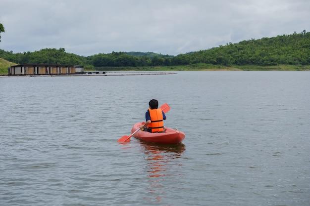 Mann, der in einem kajakboot in thailand schaufelt