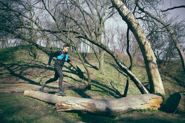Mann, der in einem park oder wald gegen baumraum läuft