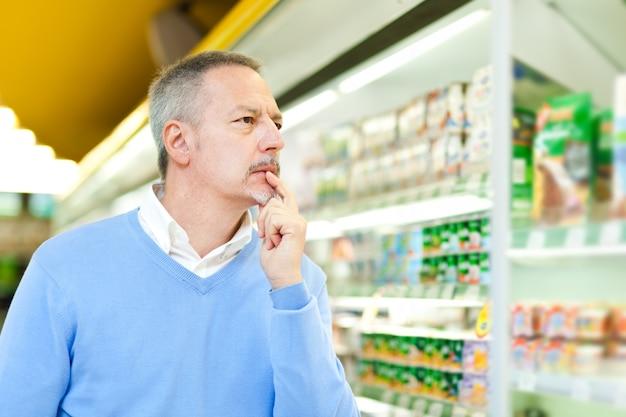 Mann, der in einem supermarkt kauft