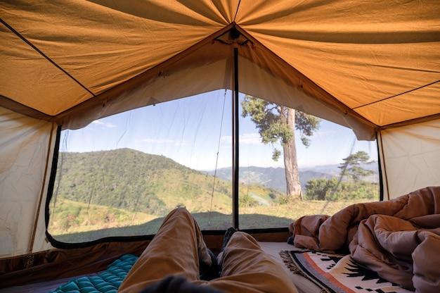 Mann, der in einem zelt auf hügel mit blauem himmel an land entspannt