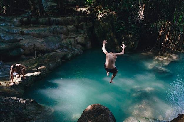 Mann, der in einen natürlichen teich springt